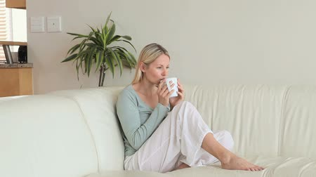 coffee time : Woman drinking coffee is sitting on a sofa in the living room
