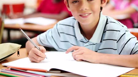 ручки : Smiling boy writing on his notebook in the classroom