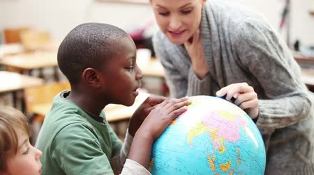 učitel : Pupil and teacher looking at a globe in the classroom