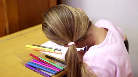 kaukázusi : Blonde girl coloring at school Stock mozgókép