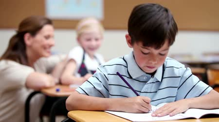 helping : Serious boy working in the classroom Stock Footage