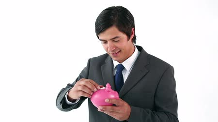 банк : Businessman putting notes in a piggy bank against a white background