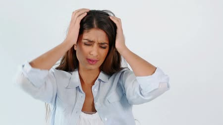 головная боль : Brunette woman showing her headache against a grey background Стоковые видеозаписи