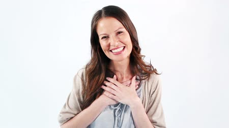 smích : Smiling woman placing her hands on her chest against a white background Dostupné videozáznamy