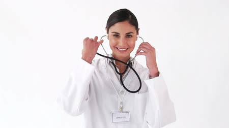 estetoscópio : Smiling nurse showing her stethoscope against a white background Vídeos