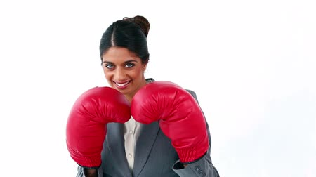 boxe : Smiling secretary using boxing gloves against a white background Vídeos