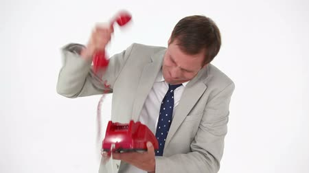 sinir : Angry man shouting in a red phone against white background