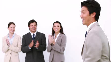 business man : Businessman being congratulated by colleagues against a white background Stock Footage