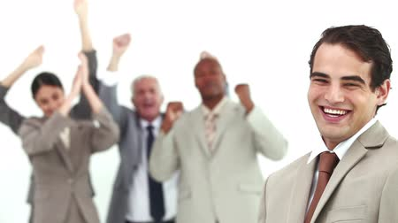 kutluyor : Man laughs while his colleagues are cheering against a white background Stok Video
