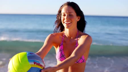 röplabda : Smiling brunette playing volleyball on the beach