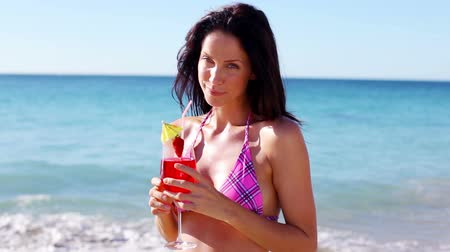 szalma : Smiling brunette drinking a cocktail on the beach Stock mozgókép