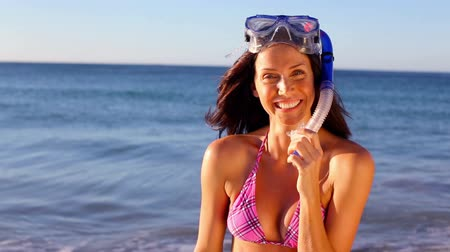 šnorchl : Smiling brunette wearing a snorkel on the beach