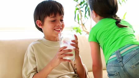 içme : Smiling siblings drinking a glass of milk in the living room Stok Video
