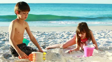 zamek : Smiling siblings building sand castles on the beach Wideo