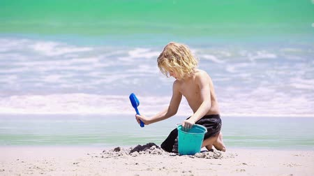 areias : Blonde child playing with a shovel on the beach