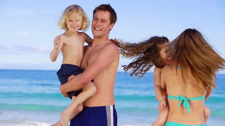 transportar : Smiling children being held by their parents on the beach