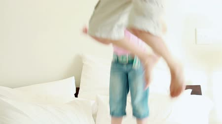 salto : Happy siblings jumping on a mattress in a bedroom