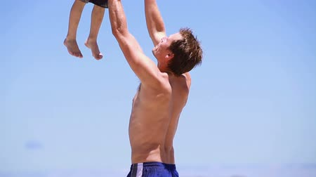 otec : Father throwing and catching his son on the beach