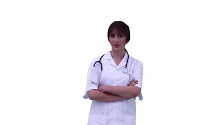 s rukama zkříženýma : Doctor crosses her arms while looking at the camera against a white background Dostupné videozáznamy