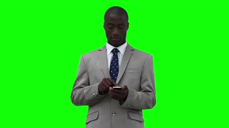 cellphone : Businessman dialing on his phone before looking upwards against a green background