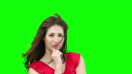 красные волосы : Woman feeling her hair as it is blown by the wind against a green background