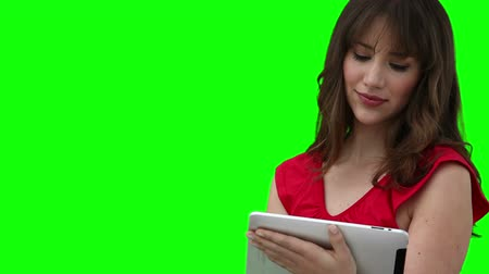 comprimido : Woman using a tablet computer against a green background