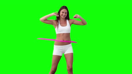 abroncs : Woman spinning a hula hoop with her arms spread against a green background Stock mozgókép