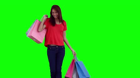 zsák : Woman dancing while holding shopping bags against a green background Stock mozgókép