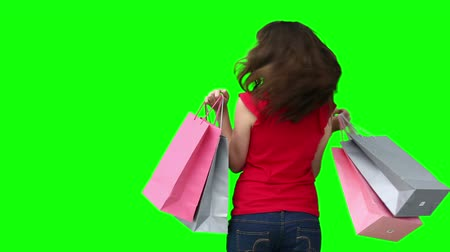 zsák : Woman smiling while holding shopping bags against a green background Stock mozgókép