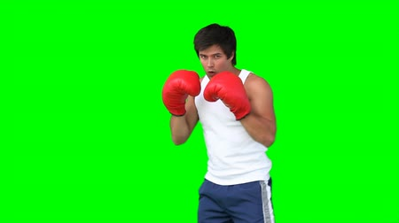 jump away : A man practises kickboxing against a green background