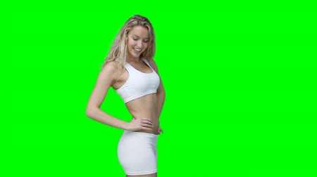 талия : A woman in training clothes posing against a green background