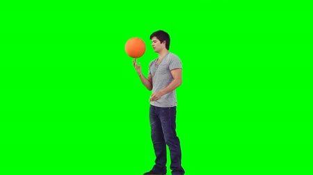 kezek : A man spinning a basketball on his hand against a green background