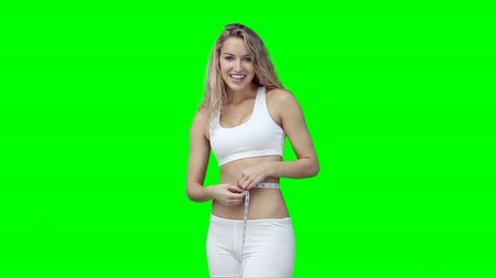талия : A woman measuring her waist line against a green background Стоковые видеозаписи