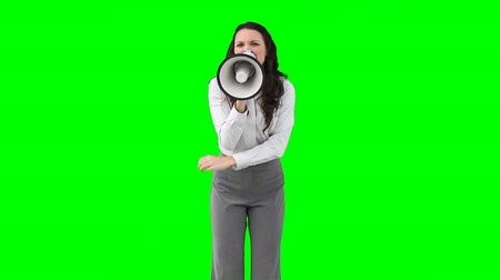 мегафон : A woman shouting angrily on a megaphone against a green background Стоковые видеозаписи