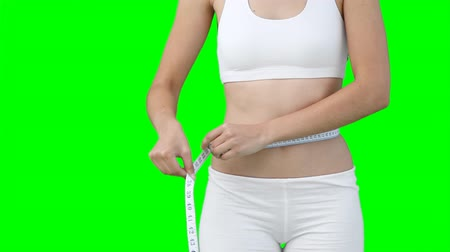 талия : A woman using a measuring tape on her waist against a green background