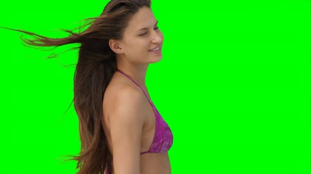 vento : A woman moving as the wind blows her hair against a green background