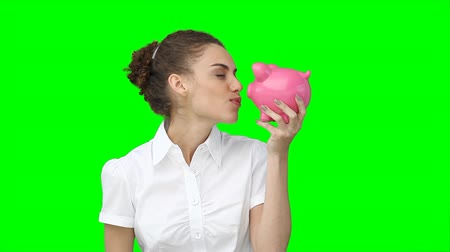 dospělý : A woman holding her piggy-bank in her hands as she shakes it while against a green background Dostupné videozáznamy