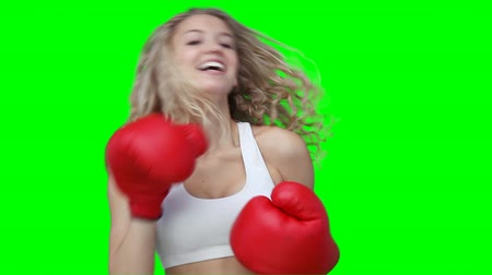 boxe : A woman punching forward at the camera while in front of a green background Vídeos
