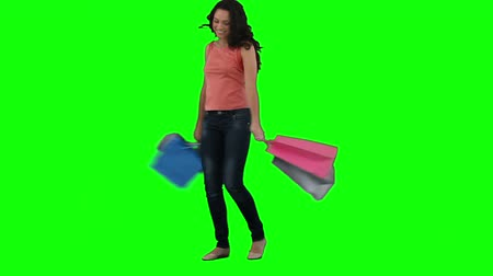 сумка : An excited woman is holding shopping bags in front of a green background