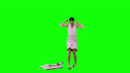 calçados : Upset woman in slow motion taking off her shoes against a green background