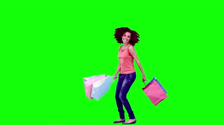 kıvırcık : Woman in slow motion holding shopping bags against a green background Stok Video