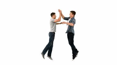 slapping : Two guys high-fiving one another in slow motion against a white background Stock Footage