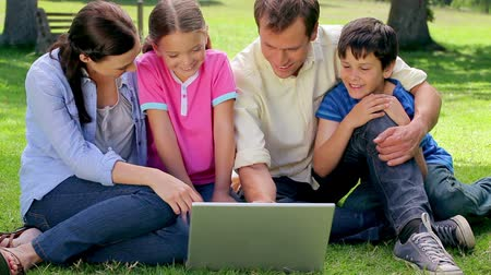 o : Smiling family looking at a laptop together while sitting in a park