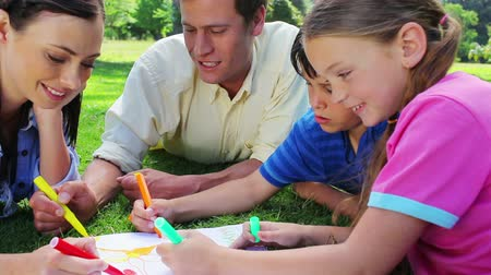 o : Smiling family coloring together in the countryside