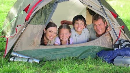 sátor : Family smiling while lying in a tent in the countryside