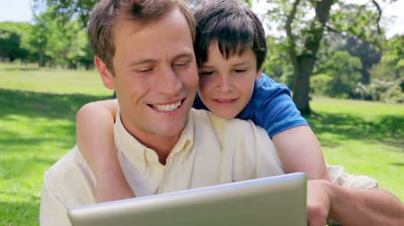 oğlum : Father and son looking at an ebook in the countryside Stok Video