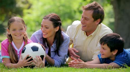 futbol topu : Smiling family trying to catch a soccer ball while lying in a park