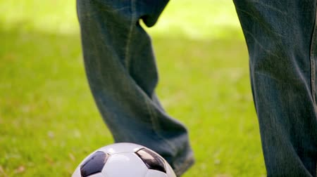 futbol topu : Little boy dribbling on the grass in the countryside Stok Video