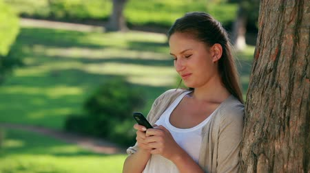 cellphone : Woman laughing while texting in a park