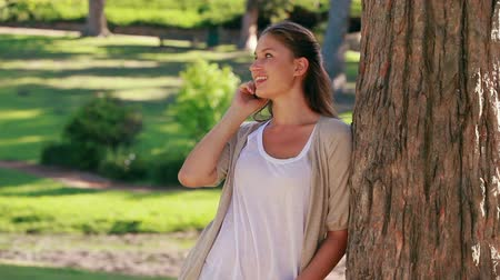 стоять : Smiling woman hanging up her mobile phone while standing in a park Стоковые видеозаписи